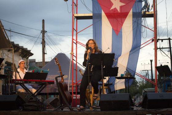 """Maria del Mar Bonet interpretant a guitarra i veu """"Què volen aquesta gent?"""" al concert número 74 de la Gira por los barrios de Silvio Rodríguez, qui desprès de cantar la cançó 'Mayor', la va presentar al públic - tot convidant-la a cantar a l'escena - com a una gran amiga, una veu extraordinària, una dona d'arrels, una llegenda. Divendres 27 de maig del 2016, al Consell Popular de Tamarindo, a Santo Suárez. (c) Juan Miguel Morales"""